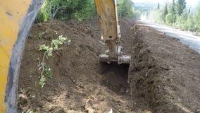 Máquina escavadora com a cubeta que escava uma trincheira filme