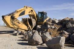 Máquina escavadora com rochas Foto de Stock Royalty Free