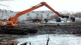 A máquina escavadora com uma cubeta larga limpa e aprofunda a cama de rio vídeos de arquivo