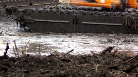 A máquina escavadora com uma cubeta larga limpa e aprofunda a cama de rio video estoque