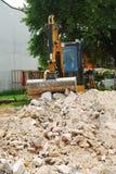 Máquina escavadora compacta no terreno de construção pequeno Imagens de Stock