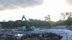 A máquina escavadora da demolição rasga fora uma construção filme