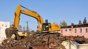 A máquina escavadora demole edifícios velhos Fotos de Stock
