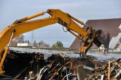 A máquina escavadora demole edifícios velhos Fotografia de Stock Royalty Free