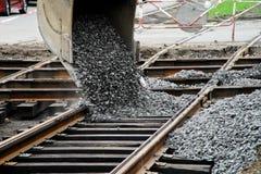 A máquina escavadora derrama o cascalho nos trilhos do bonde Repare a estrada r fotografia de stock royalty free