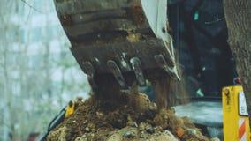 A máquina escavadora derrama a terra fora da cubeta vídeos de arquivo
