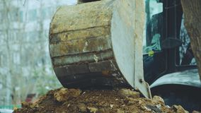 A máquina escavadora derrama a terra fora da cubeta filme