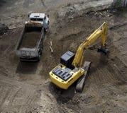 Máquina escavadora e caminhão de descarga fotografia de stock