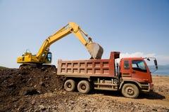 Máquina escavadora e caminhão de descarga pesado fotografia de stock