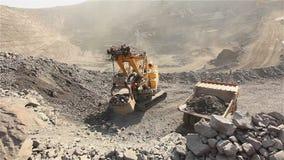 A máquina escavadora e o descarregador na pedreira, grande máquina escavadora amarela carregaram o minério em um descarregador, e video estoque