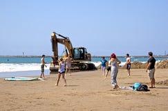Máquina escavadora e oito povos na praia em Durban Fotografia de Stock