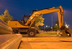 Máquina escavadora em a noite Imagem de Stock