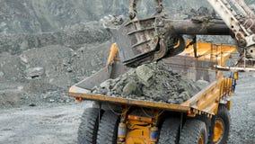 A máquina escavadora enche o caminhão basculante O close up da máquina escavadora da cubeta carrega pedras no corpo do caminhão b vídeos de arquivo