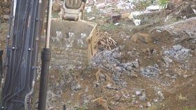 A máquina escavadora esmaga uma cubeta das rochas ao lado de uma terra suja filme
