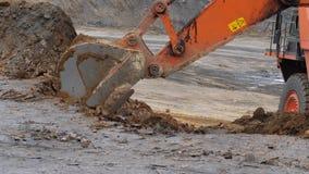 A máquina escavadora está escavando o solo no close-up A cubeta da máquina escavadora ajunta o solo de argila Abra Pit Mining Mov video estoque