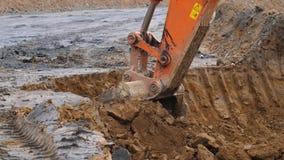 A máquina escavadora está escavando o solo no close-up A cubeta da máquina escavadora ajunta o solo de argila Abra Pit Mining Mov filme