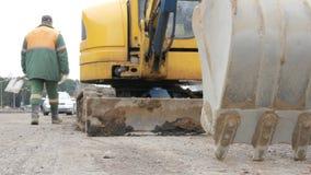 A máquina escavadora está na estrada com a cubeta abaixada Os trabalhos de estrada são realizados na cidade filme
