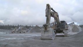 A máquina escavadora está no fundo de uma fábrica de tratamento de pedra vídeos de arquivo