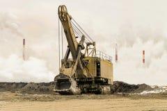 Máquina escavadora grande da mineração da cubeta em uma trilha da esteira rolante contra um fundo da poluição atmosférica e da né Foto de Stock Royalty Free