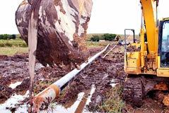 M?quina escavadora Holding Pipeline no p?ntano imagens de stock royalty free