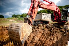 Máquina escavadora industrial que escava um furo e que carrega a terra fotografia de stock