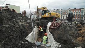 Máquina escavadora na areia da descarga do terreno de construção dentro à vala com os dois trabalhadores nos capacetes de seguran video estoque