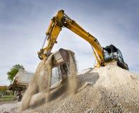 Máquina escavadora na pilha do cascalho fotos de stock royalty free