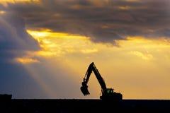 Máquina escavadora no por do sol Fotos de Stock Royalty Free