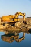 Máquina escavadora oxidada velha que escava na lama imagem de stock