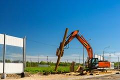 Máquina escavadora para martelar as pilhas de aço, estrada da construção imagens de stock