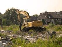 Máquina escavadora que demole sobras da construção Foto de Stock