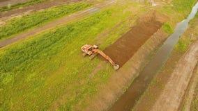 Máquina escavadora que escava uma trincheira no campo Vídeo aéreo vídeos de arquivo