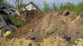 Máquina escavadora que faz trabalhos da terra com a casa de campo no fundo filme