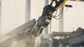 Máquina escavadora que remove as sobras da casa arruinadas pelo ataque da catástrofe natural ou de terror video estoque
