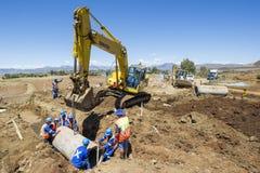 Máquina escavadora que trabalha na estrada Fotos de Stock Royalty Free