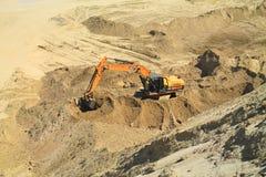 Máquina escavadora que trabalha na parte inferior da pedreira em um dia ensolarado Imagens de Stock Royalty Free