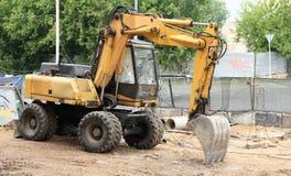 Máquina escavadora rodada na terra Imagem de Stock Royalty Free