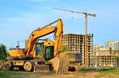 Máquina escavadora seguida pesada em um canteiro de obras em um fundo de uma construção residencial e em guindastes de construção fotos de stock royalty free
