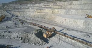 A máquina escavadora superior da vista carrega carros de trem de mercadorias com a rocha vídeos de arquivo