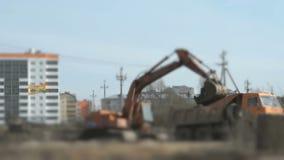 A máquina escavadora transfere arquivos pela rede uma argila em um caminhão usando uma cubeta filme