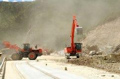 Máquina escavadora vermelha que opera-se na montanha foto de stock royalty free