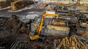 A máquina está levantando a madeira serrada em uma fábrica de madeira Opinião do olho do ` s do pássaro imagens de stock royalty free
