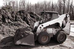Máquina hidráulica do carregador do boi do patim na pilha do Mulch Fotografia de Stock