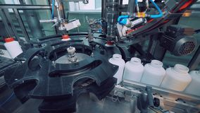 A máquina industrial é tampões de parafusamento aos frascos plásticos vídeos de arquivo
