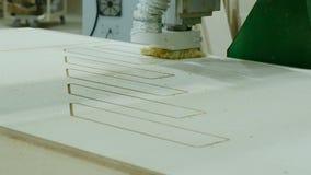 Máquina moderna do woodworking na ação Corta partes encaracolados da folha da madeira compensada Produção de mobília de madeira filme