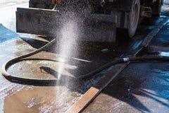 A máquina municipal derrama a estrada com uma mangueira danificada imagem de stock
