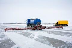 A máquina para a distribuição de reagentes antigeadas líquidos na pista de decolagem e na máquina do vassoura-vácuo no aeródromo foto de stock