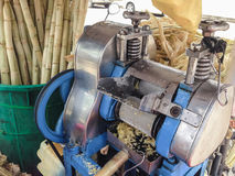 A máquina para faz o suco da cana-de-açúcar com fundo do cana-de-açúcar de imagens de stock
