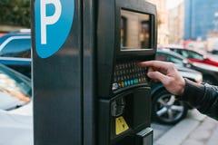 Máquina para pagar el estacionamiento Un hombre hace clic en los botones de la máquina del estacionamiento en ciudad europea Foto de archivo