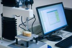 Máquina que analiza la rebanada de pan con el ordenador Foto de archivo libre de regalías